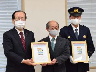 元日に遠野市内全世帯に届けられるはがきを手にする(左から)本田敏秋市長、汀工社長、亀山久雄署長