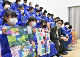 作品を商品化したアートハンカチなどを手にする生徒と記念撮影する松田文登副社長(前列左から4人目)。バックホーのラッピング企画が進んでいる