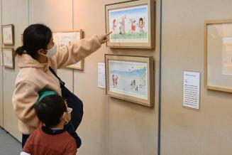 加古里子さんの絵に見入る来場者=12日、盛岡市・市民文化ホール