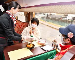 日本航空客室乗務員の高瀬雅子さんから瓶ドンを受け取る乗客
