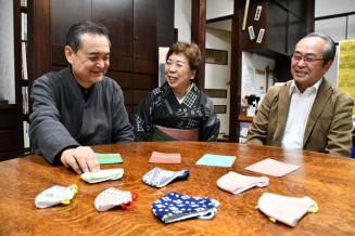 共同開発した飲食用マスクとマスクケースを前に普及拡大を目指す(左から)佐藤敏孝代表、佐藤美津子店長、高橋一男代表取締役