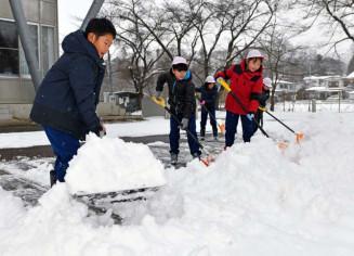 一戸南小の校内で雪かきに励む児童=14日、一戸町西法寺