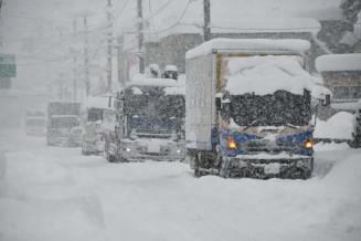 大雪のため国道107号で立ち往生する大型トラック=16日午前11時40分、北上市和賀町横川目
