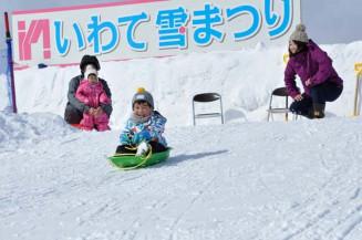 そり滑りを楽しむ第53回いわて雪まつりの来場者。新型コロナウイルス感染症の影響で来年は初の中止が決まった=2020年2月、雫石町