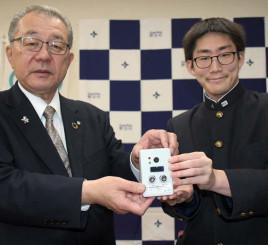 小田祐士村長に非接触型体温計を手渡す石原福太郎さん(右)