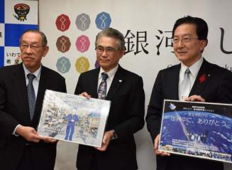 県産米「銀河のしずく」の宇宙打ち上げを紹介する長谷川洋一代表理事(中央)ら