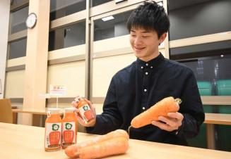素材のニンジンと開発したジュースを手にする増田侑十代表
