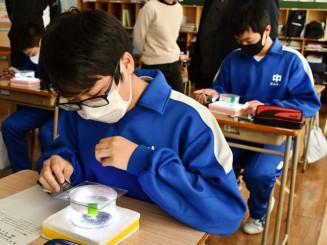 ドライアイスとアルコールを使い、粒子が通った跡を観察する生徒
