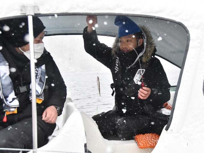 雪の降る中、ワカサギ釣りを楽しむ来場者
