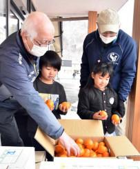 被災地に思いを寄せる人々が育てた静岡県産ミカンを手にする園児ら