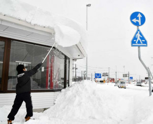屋根に積もった大量の雪を棒で払い落とす店員=21日正午、平泉町平泉