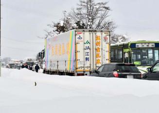 県道脇に積まれた雪で道幅が狭くなり、すれ違いに苦労するバスやトラック。周辺では事故の影響で約2時間渋滞した=22日午後1時38分、奥州市水沢佐倉河(写真は一部加工しています)