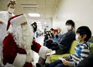 診療を待つ患者に笑顔でマスクをプレゼントするサンタクロース