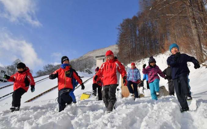 青空の下、「イチ、ニッ、イチ、ニッ」と声を合わせて雪を踏み固める田山スポーツ少年団の子どもたち=26日、八幡平市矢神・田山スキー場