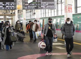 大きな荷物や土産物を手にするマスク姿の帰省客ら=27日、盛岡市・JR盛岡駅
