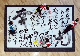 巨大な紙にメッセージを書き上げる宮古高と宮古商工高の書道部員