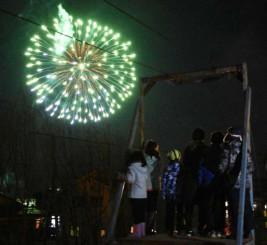 林郷小の校庭で歓声を上げながら花火を眺める子どもら