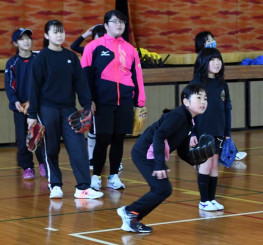 屋内施設でテニスボールのノックを受ける選手たち