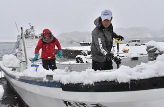 寒空の下、漁船に積もった雪をかく漁業者=30日、宮古市日立浜町