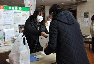 山屋理恵理事長からおせち料理を受け取る女性(右)