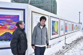 「仮囲いアート」として作品を展示している田崎飛鳥さん(右)と父実さん