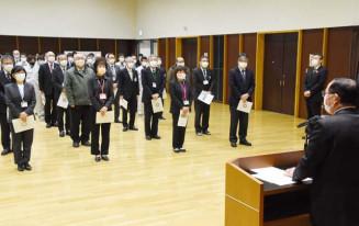 田村正彦八幡平市長(右)の訓示を聞く職員。例年より会場を広くした