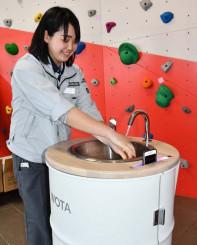 スマートフォンを除菌しながら「WOSH」で手を洗う北良の従業員