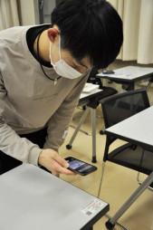 患者が確認された際の対応につなげるため、座席に貼られた2次元コードをスマートフォンで読み取る盛岡大の学生