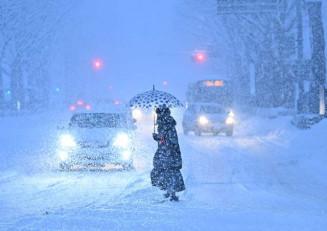 雪が激しく降り、視界不良となった盛岡市内。車はライトをつけて走行した=7日午後4時14分、盛岡市内丸