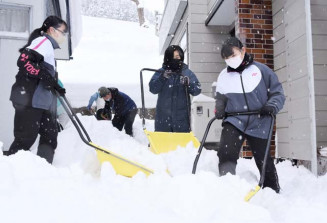 対象世帯の雪かきに励む安代中の生徒らスノーバスターズの隊員
