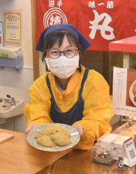 秋田のハタハタと三陸のタラを合わせた「海恋コロッケ」を手にする徳江邦子社長