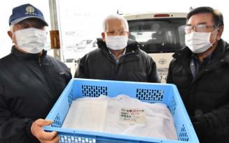 秋田県大仙市から届いたサケの受精卵を手に笑顔を見せる漁協関係者