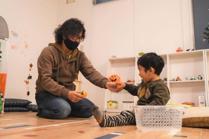 手慣れた様子で子どもの相手をする田中大樹さん。保育士経験を生かして託児事業を展開する