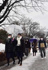 雨の中、試験会場に向かう受験生=16日、盛岡市上田・岩手大学