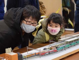 夢中になってジオラマの中を走る列車を見つめる親子連れ