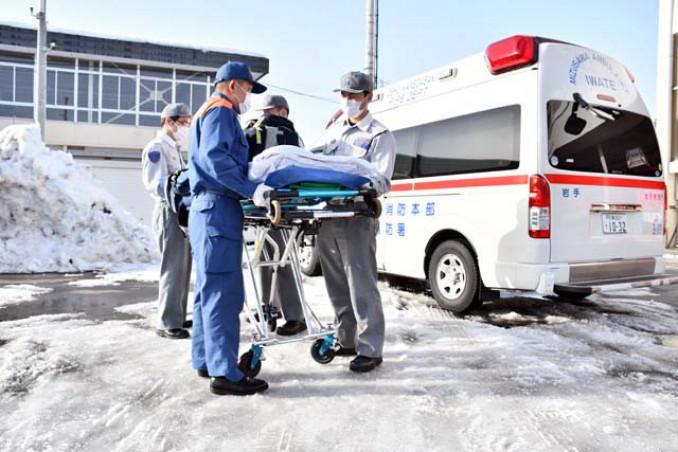 大雪の影響で、4人態勢でストレッチャーを動かす消防職員