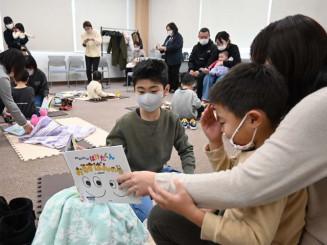 ぬいぐるみに絵本を読み聞かせる子どもたち