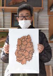 本県の地図をイメージした木工パズルを製作した荒屋治彦さん
