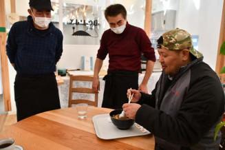 植山竜太郎店主(中央)の考案したもみじラーメンを試食する兼沢幸男社長(右)