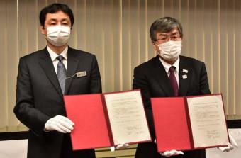 多言語電話通訳サービスの覚書を示す紺野純一専務理事(右)と大塚健滋警務部長