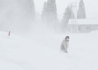 激しい地吹雪の中、雪かきに追われる女性=19日、雫石町南畑