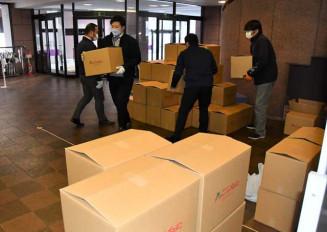 花巻市から寮生向けに寄付された食料品が入った段ボール箱を仕分ける富士大関係者=19日、同市下根子