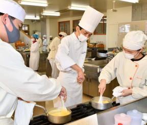 佐藤充弘シェフ(中央)の指導を受けながら、調理に励む大船渡東高の生徒