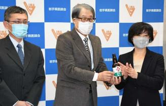 小原紀彰会長(中央)、久保田公宜常任理事(左)にビールによって広がった善意を伝える新里佳子社長(右)