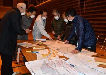 ワークショップで過去の被災状況を地図上に書き込んでいく町民ら