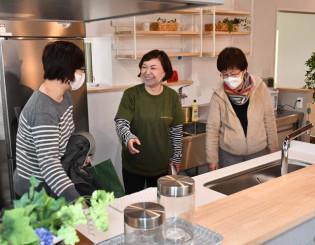 イベント参加者にキッチン設備について説明する佐々木江美社長(中央)