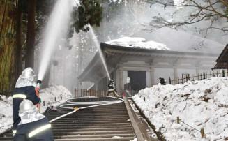 中尊寺での訓練で警戒放水する消防署員ら