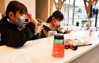 3月11日の催事に向け、プラスチック製コップに絵を描く参加者