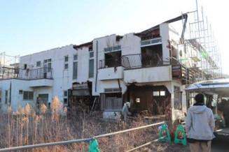 解体に向け本格的作業が始まった旧「民宿あかぶ」=25日午前、大槌町