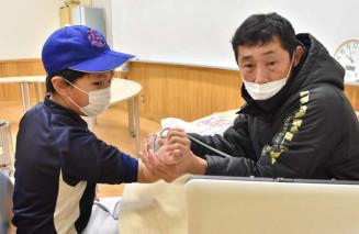 大歳憲一医師から肘の超音波検査を受ける小学生